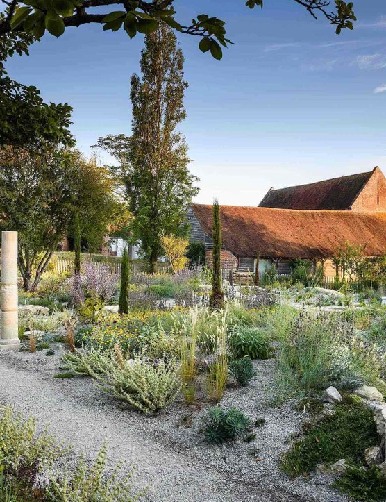 Thin pencil cypresses work and stone columns to provide strong verticality from the ground-level planting. This helps draw the poplar growing just outside the garden into the composition