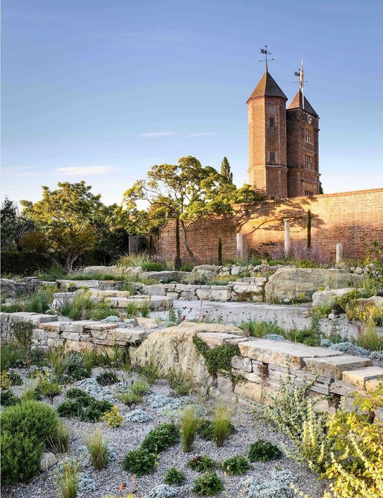 Looking back towards Sissinghurst's iconic Tower, plants occupy the shady side of the stone wall while others colonise the cracks