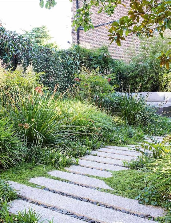 The layered planting in the large bed obscures the seating area from view. A path, softened by mats of Ophiopogon planiscapus, Soleirolia soleirolii and Viola hederacea, slows down the journey to the end of the garden