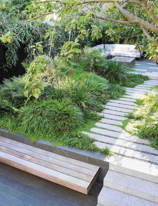 The garden is unified by repeat evergreen planting and hard landscaping, incorporating a calming blend of dark-grey and pale elements of the main path and rear terrace