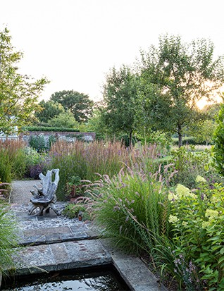 Looking along the back of the house, a two-tier water feature makes a virtue out of a step down in the levels. The driftwood 'throne' sitting on a carpet of flint doubles as sculpture amid a sway of lime-green Hydrangea paniculata 'Limelight' and fluffy, pink Pennisetum orientale 'Karley Rose