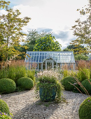 Amid a pared-back mix of Calamagrostis x acutiflora 'Stricta', Amelanchier x grandiflora 'Robin Hill' and box balls, recycled cobbles and a traditional-style greenhouse give the Ornamental Garden a timeless air. Within the central circles of cobbles, a verdigris planter acts as a focal point.