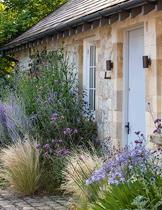 In one narrow bed Jane has orchestrated a long season of interest in soft, smoky shades that complement the stone walls behind them. Echinops ritro 'Veitch's Blue', Verbena bonariensis, Salvia 'Blue Spire' and Agapanthus Headbourne hybrids form a harmonious tapestry of lavenders and blues interspersed with silvery clumps of Artemisia 'Powis Castle', while pale plumes of Stipa tenuissima frame the doorway.