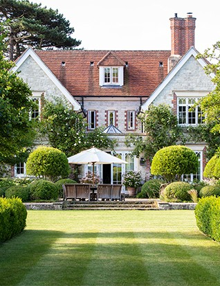 At its most formal, the rear elevation of the house is framed by an avenue of Crataegus persimilis 'Prunifolia' edged in low box hedges, although the bedroom windows are festooned with a charming combination of Trachelospermum jasminoides and repeat-flowering old rose 'Madame Alfred Carrière'.
