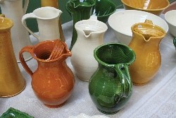 A selection of orange, mustard, green and white clay jugs found at a brocante in France