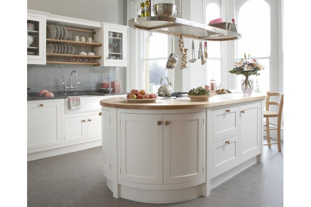 A sage and cream painted kitchen featuring worktops in maple and green slate