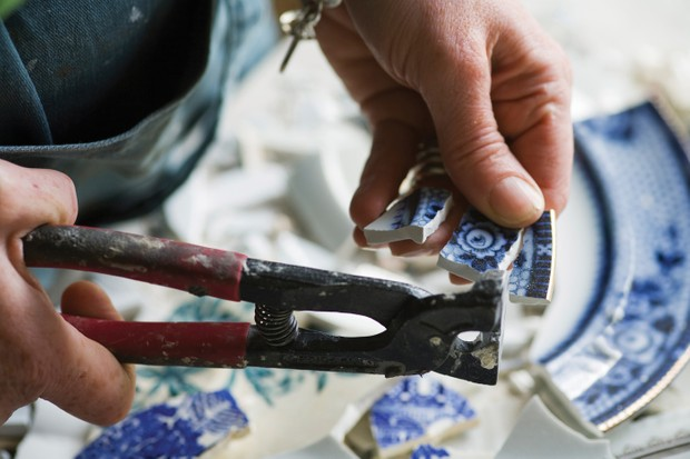 Cleo Mussi working on broken pieces of a china plate