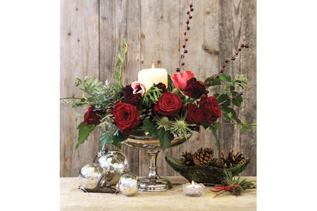 A silver pedestal vase filled with red roses, greenery and a lit pillar candle