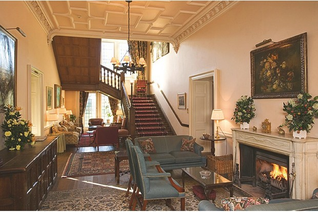 The entrace of the Ballathie House Hotel in Perthshire featuring a sweeping staircase and antique blue sofas