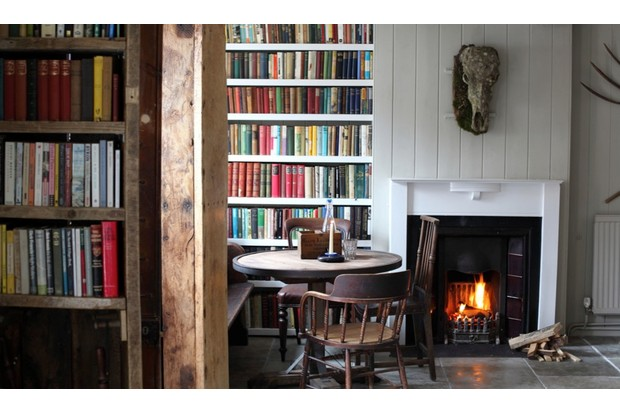 The interior of the Black Lion feating a bookshelf and a roaring fire