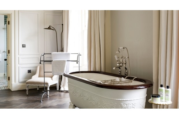An antique bathtub in a pale grey room at No. 131 in Cheltenham