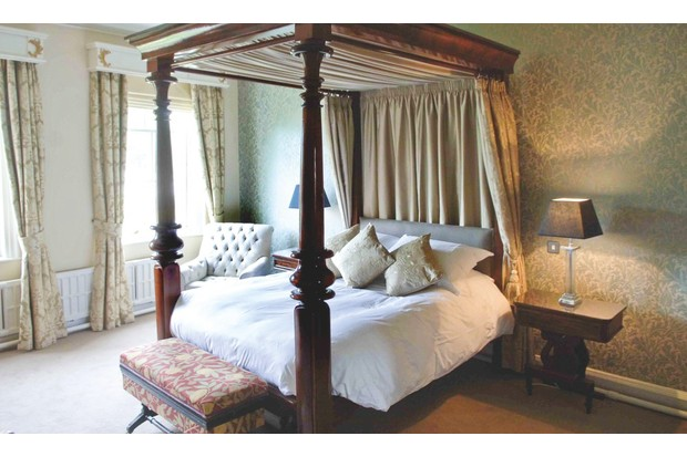 A bedroom at Grays Court featuring a brown four-poster bed and floral wallpaper