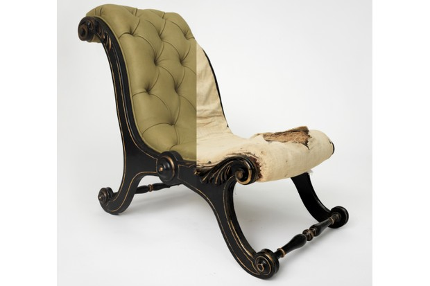 An antique button-back chair with half of the upholstery removed