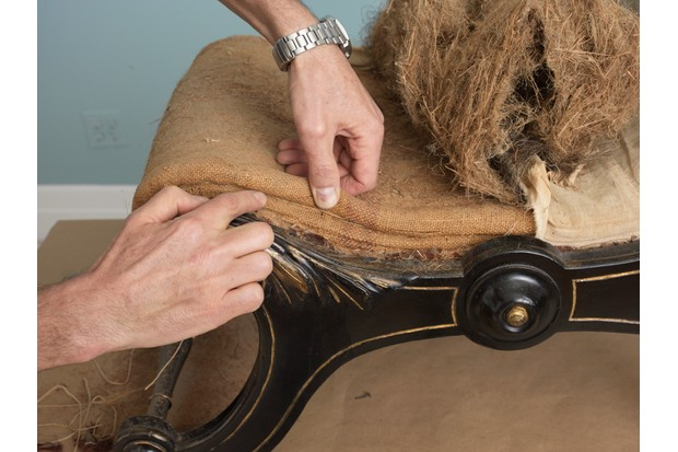 Someone peels back the upholstery on an antique dining chair