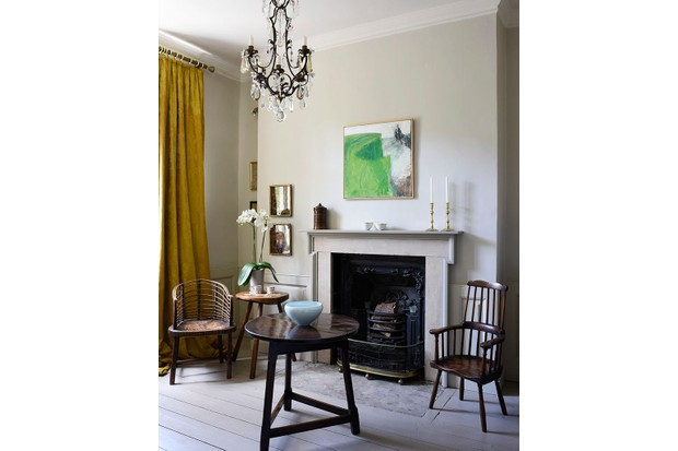 In this room, a chandelier hangs above a Welsh oak cricket table in front of a fireplace