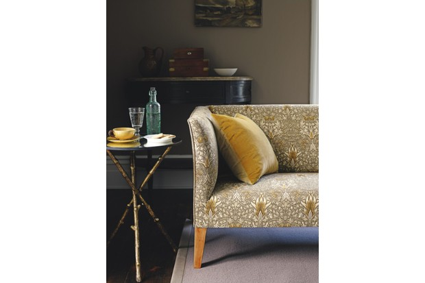 An Art Deco style sofa upholstered in yellow William Morris fabric against a dark living room wall