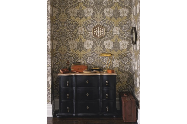 An antique sideboard painted black sits in front of patterned William Morris wallpaper