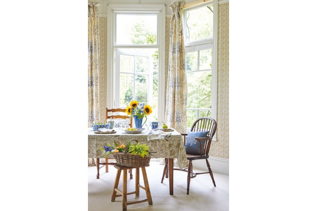A summer dining scene: a table is covered with a William Morris table cloth and William Morris curtains hang behind