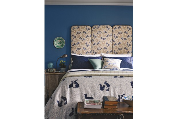 A headboard upholstered in William Morris fabric in a dark blue bedroom