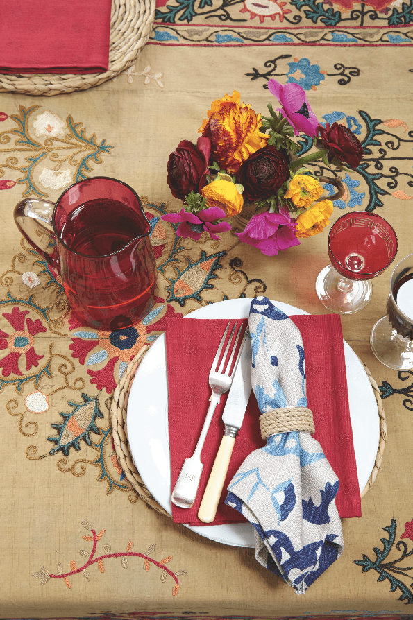 A dining table covered in an antique Suzan with red cranberry glasses, white plates, vintage cutlery and Suzani napkins