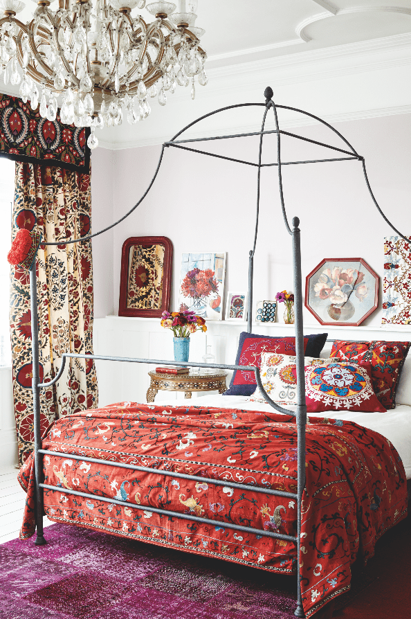 A metal four poster double bed with an antique suzani being used as a bedspread