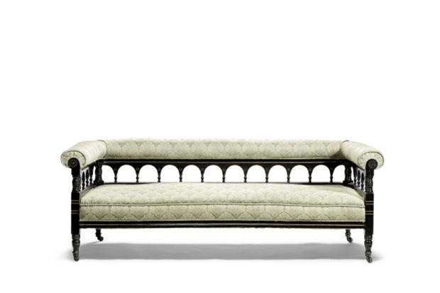 An antique sofa with pale cream cushions and a cut-out back