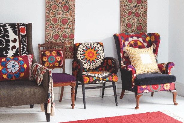 Three armchairs upholstered in Suzani fabric behind Suzan panels