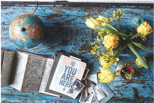 A distressed blue table with an antique globe, map and vase of fresh yellow flowers