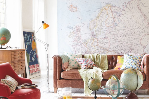 A living room with a brown leather sofa, red armchair and a coffee table littered with antique globes. A large antique map hangs on the wall behind the sofa.