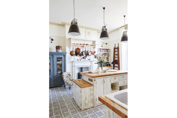 A farmhouse-style white kitchen with blue patterned floor tiles. A collection of vintage copper pans hangs above the fireplace, alongside a painted blue armoire.