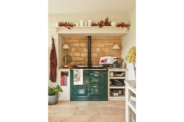 A dark green AGA against exposed brickwork in a farmhouse kitchen.