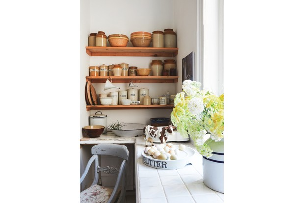 A display of brown pottery and food storage jars in an old-fashioned kitchen. An overflowing vase of gypsophila is in the foreground.