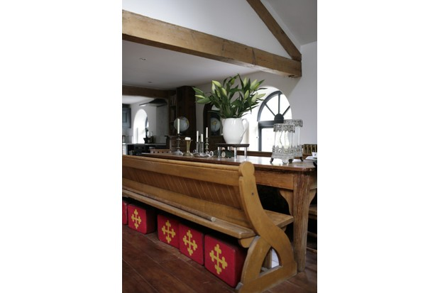 Reclaimed vintage church pews are used as dining room benches in Drew Pritchard's home.