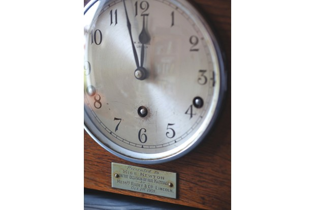 The face of the clock. A metal tag reads 'Presented to Miss Newton, on the occasion of her marriage, Oct. 1st 1938'