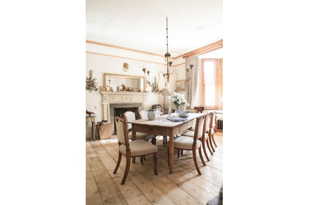 The dining room in Spencer and Freya Swaffer's home features an antique farmhouse table, upholstered dining chairs and a large antique pendant light