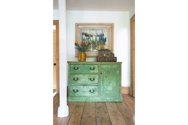 A vintage, distressed green dresser with a 1920s painting above it