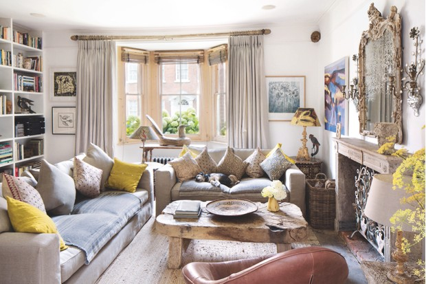 Freya and Spencer Swaffer's living room with two large grey sofas peppered with mustard cushions, a reclaimed wood coffee table and an ornate gilded mirror hanging above the fireplace