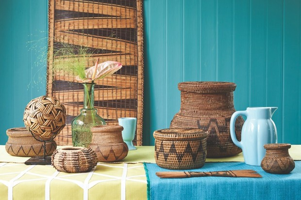 A table with a lime green and blue table cloth adorned with woven rattan bowls, baskets and panels