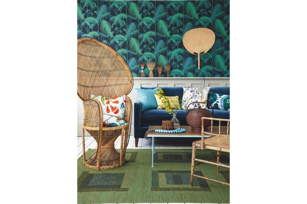 A living room scene with palm-printed wallpaper, a deep blue velvet sofa, a mid-century coffee table and a rattan peacock chair