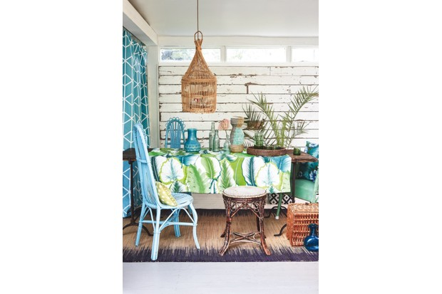 An outdoor table scene with blue woven chairs and a palm-printed table cloth