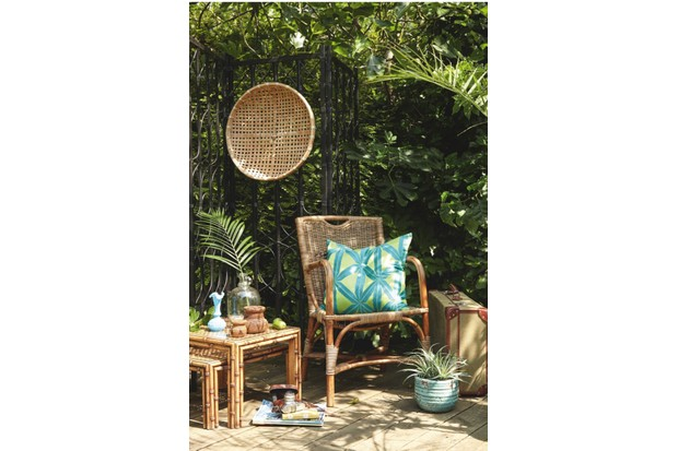 An outdoor scene featuring a woven rattan chair and side table