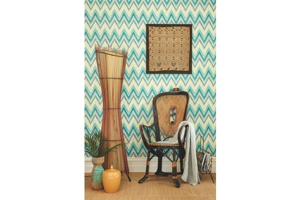 A rattan armchair and tall rattan lamp in front of green and blue zigzag wallpaper