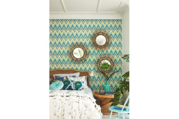 A double bed with a woven rattan headboard against green and blue zigzag wallpaper with three rattan mirrors