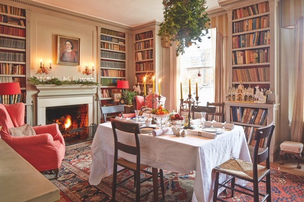 A cosy library in a period home with a dining table in the centre