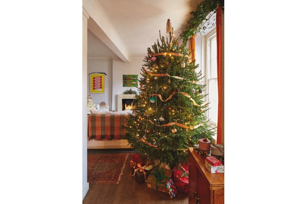 A large real Christmas tree adorned with strands of lametta, orange ribbon and vintage baubles
