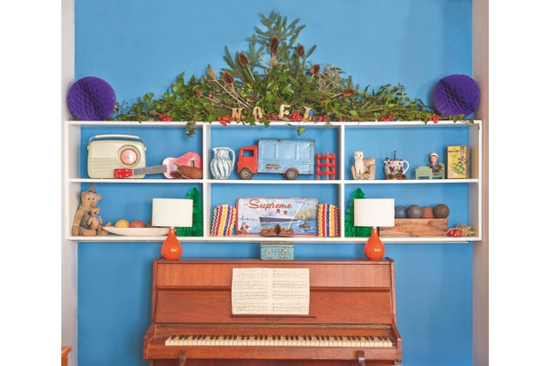 A vintage brown piano in front of a bright blue wall and shelves of vintage toys and books