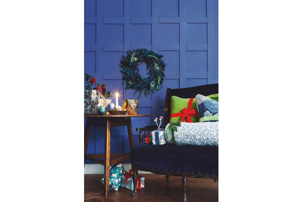 Blue velvet chair next to an arts and crafts table against a vibrant blue background Presents wrapped in Emily Burningham wrapping paper, ribbons tied around patterned cushions, art deco baubles, Morris & Co accessories and arts and crafts antiques