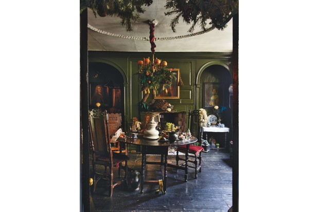 The dining room in Dennis Severs' House with a dark wood table, dark green walls, oil paintings and a chandelier adorned with greenery and oranges
