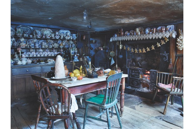 A low-ceilinged basement kitchen in Dennis Severs House with an open fireplace, a welsh dresser laden with china and a kitchen table laden with Christmas food