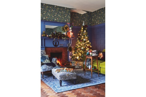 William Morris armchair in a Christmassy living room next to a fire. Christmas tree is filled with lights and stands next to a green velvet sofa and arts and crafts movement table. William Morris wallpaper reflected in mirror